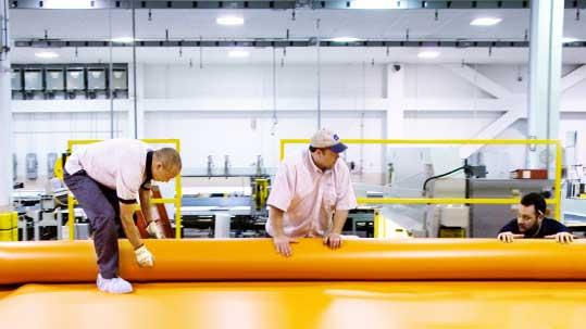 Forbo Mitarbeitende in der Produktion mit orangem Forbo Siegling Transilon Transportband.