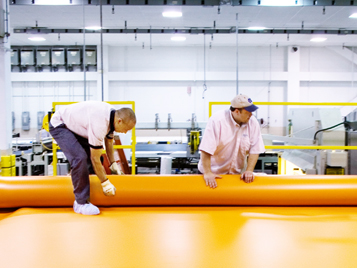 Forbo employees in production with orange Forbo Siegling Transilon conveyor belt.