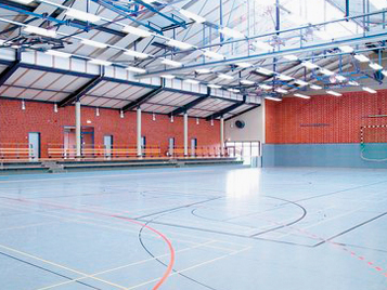 Sports flooring: gym hall with blue Forbo linoleum sports floor covering.