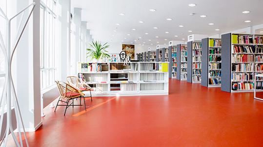 Bildungswesen: Bibliothek mit rotem Forbo Linoleum Boden.