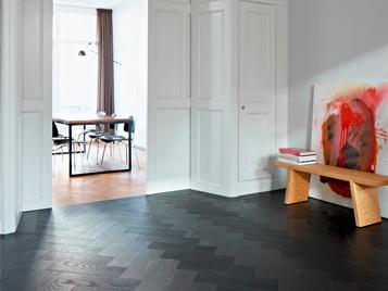 Privater Wohnbereich: Wohnsituation mit schwarzem Forbo Allura Luxury Vinyl Boden und offener Tür zu weiterem Zimmer.