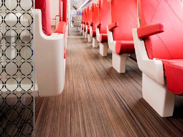 Transport: Ausschnitt aus einem Eisenbahnwagen mit dunklem gestreiften Forbo Boden Marmoleum Striato und roten Sitzplätzen.