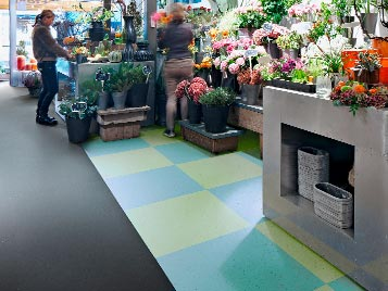 Retail and shop fitting: colored LVT floor (Forbo Allura Luxury Vinyl Tiles) at the sales point of a garden department.