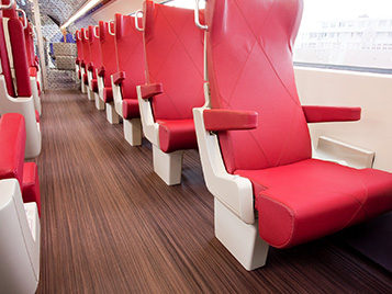 Transport: section of a railway carriage with dark striped Forbo floor Marmoleum Striato and red seats.